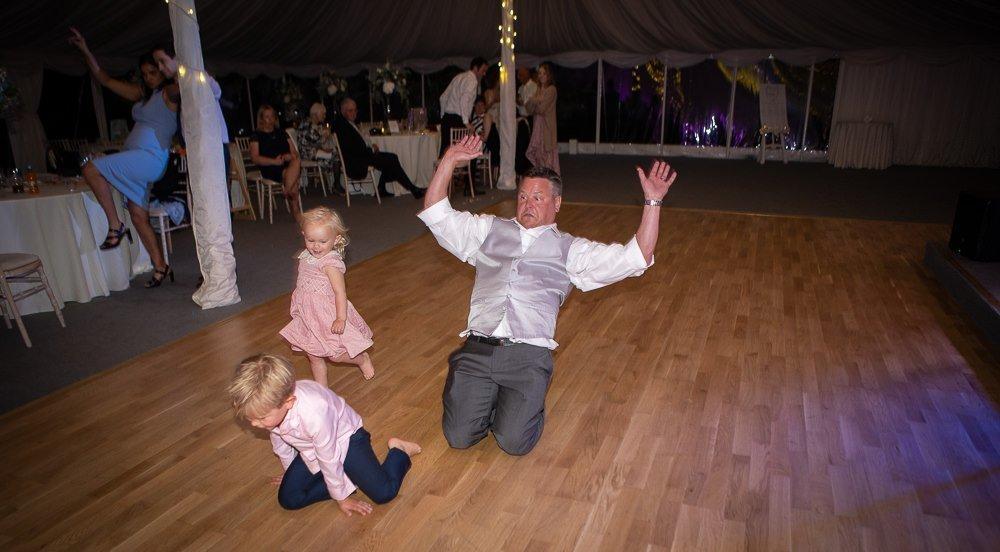 Grown ups and kids skidding on the dance floor at Longstowe Wedding