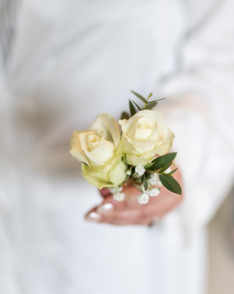 Bride holding button hole flower at Longstowe Wedding