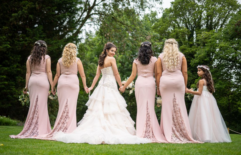 image showing the back of the bridal party's dressed, with bride looking back.