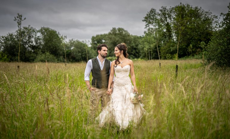 Sheene Mill Wedding Couple Standing in a meadow looking towards each other.