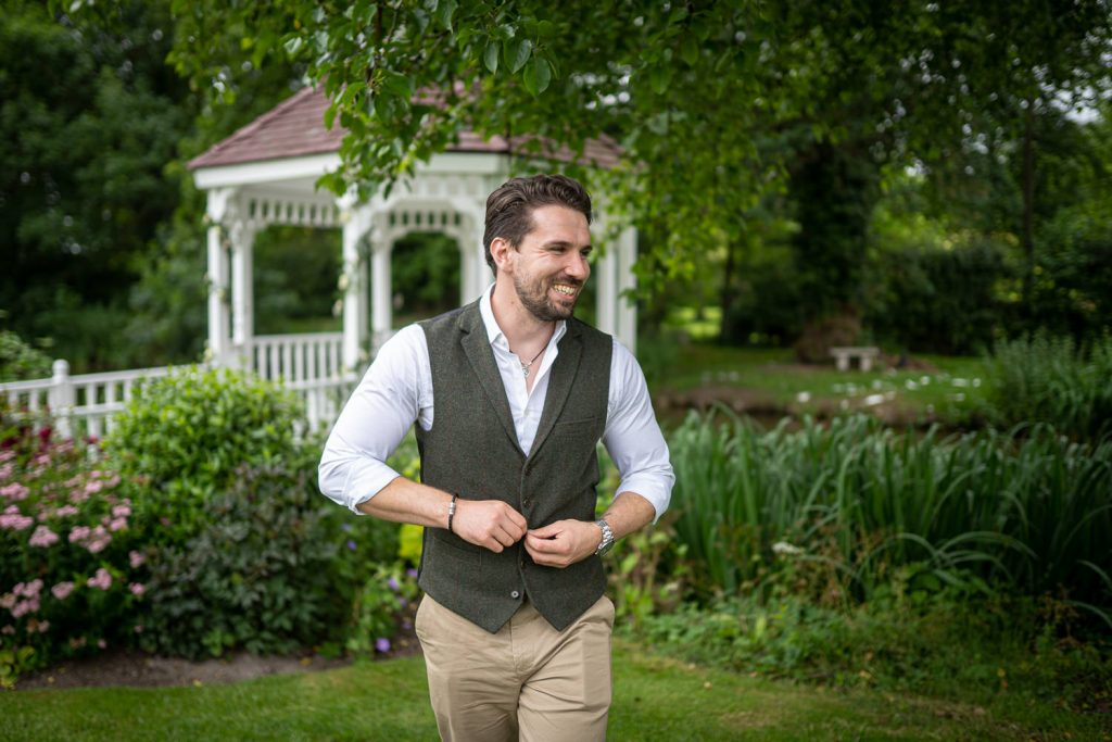 Groom walking and laughing as he buttons his waist coat