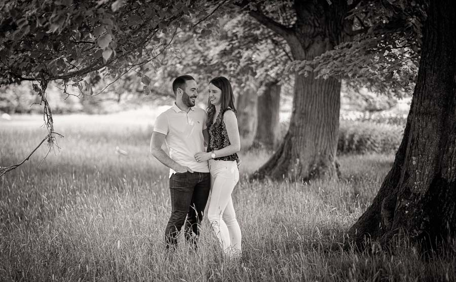 Couple standing in woodland during their engagement shoot cambridge