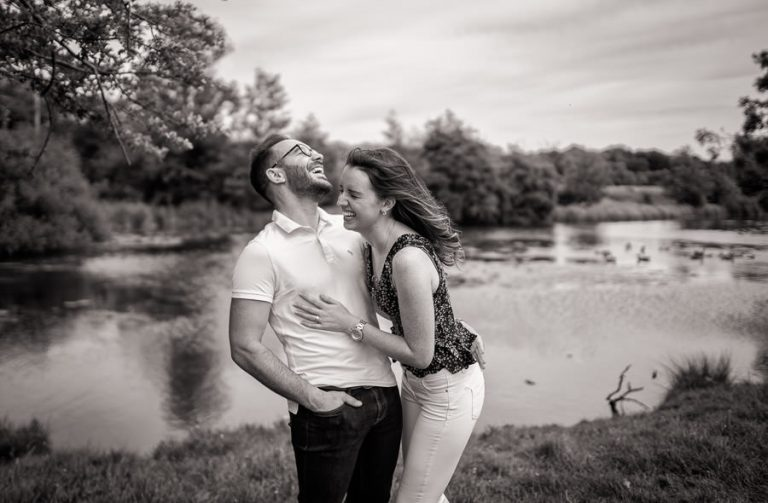 Couple laughing during their engagement shoot cambridge, photographed in black and white by Cambridge wedding photographer