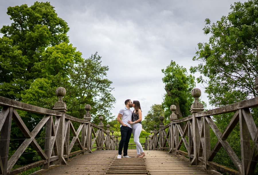 couple kissing on an old bridge.