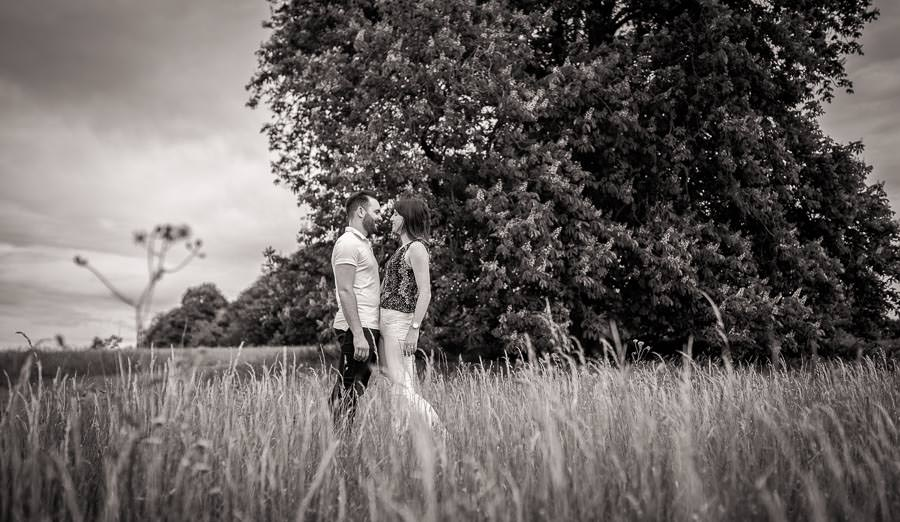 couple standing in a long grassed meadow. Photographed by Cambridge Wedding Photographer