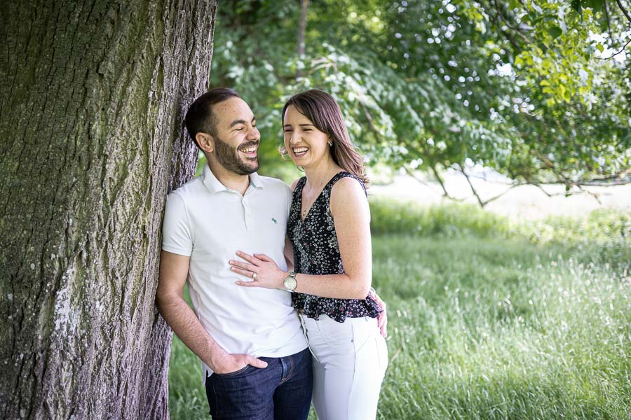 Couple leaning by a try and laughing during their engagement shoot cambridge