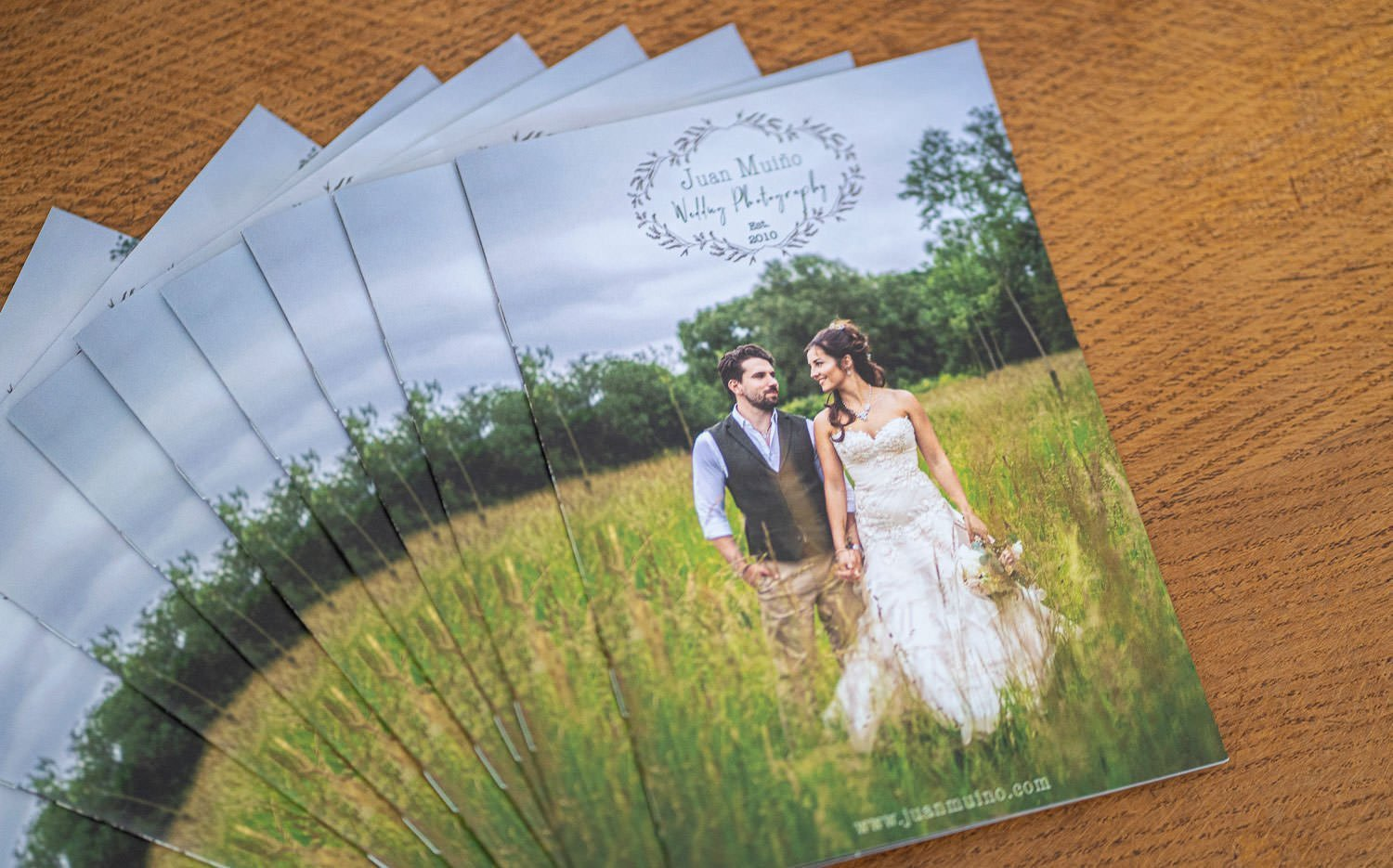 collection of our wedding photography brochure fanned out on a table.