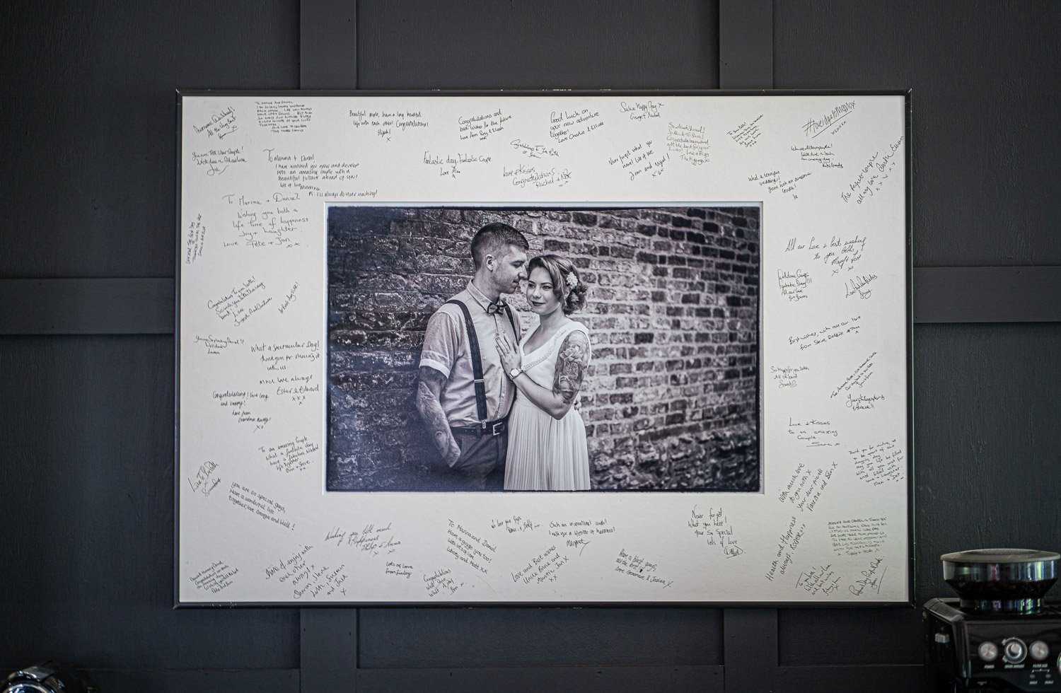 signing frame hanging on a panelled wall, showing all the signatures as well as the couple in a black and white image.