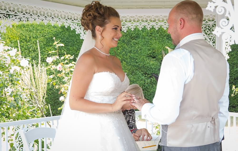 Bride placing a ring on grooms finger during wedding ceremony