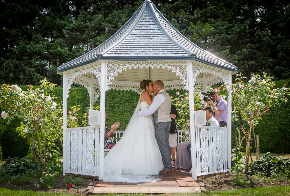 Bride and Groom kissing during their ceremony at Hockwold Hall Wedding