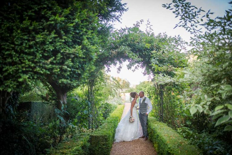 Bride and Groom Kissing in the gardens at Hockwold Hall Wedding