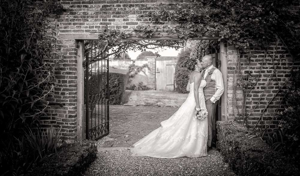 black and white image of bride and groom kissing in an archway at Hockwold Hall Wedding
