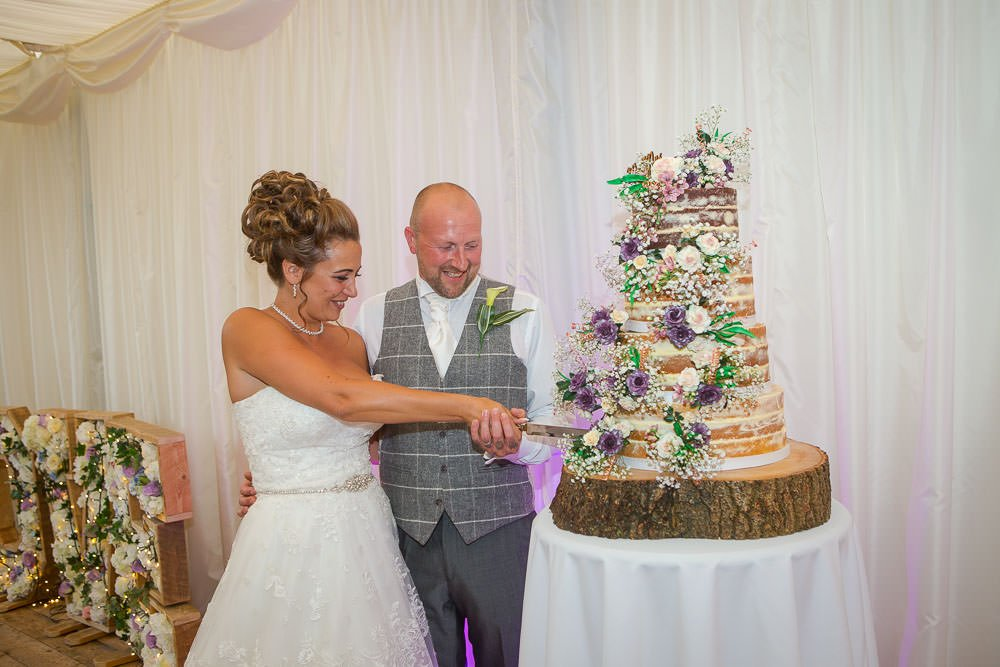 Bride and groom cutting their cake at a Hockwold Hall Wedding