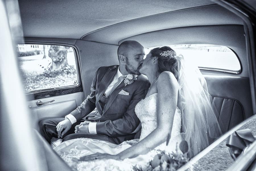 Lanwades Hall Wedding image of bride and groom kissing in a vintage Bentley wedding car.