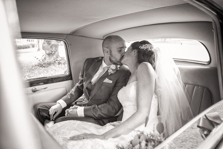 Bride and groom kissing in a car, photographed by Cambridge Wedding Photographer at Lanwades Hall Wedding
