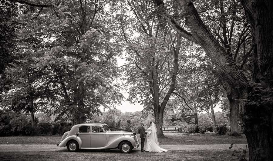 Black and white wedding photograph of couple standing by a Vintage Bentley wedding car at Lanwades Hall Wedding