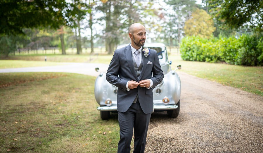 Groom standing in front of the vintage Bentley parked at a Lanwades Hall Wedding
