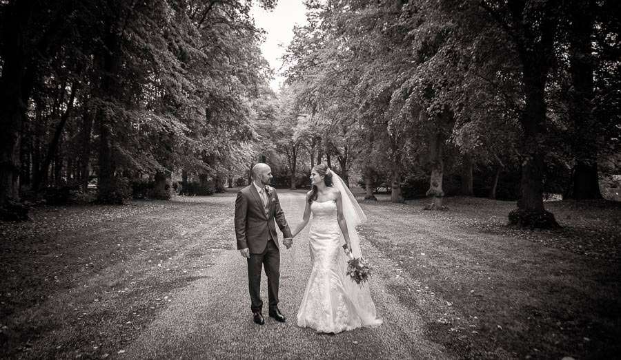 Black and white wedding photograph of bride and groom walking along tree lined avenue at Lanwades Hall Wedding