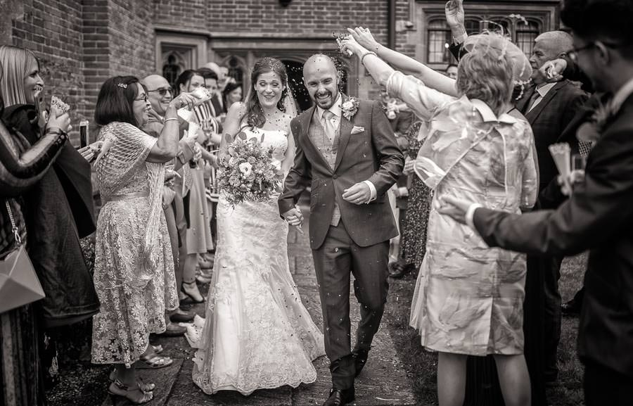 Black and white wedding photograph of bride and groom walking through a confetti parade at a Lanwades Hall Wedding