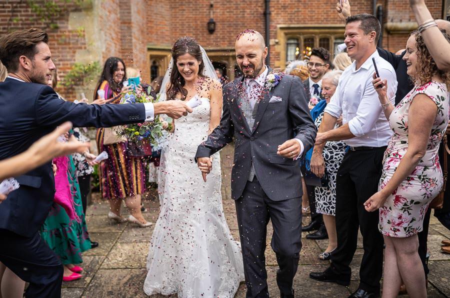 bride and groom walking through a confetti parade at a Lanwades Hall Wedding