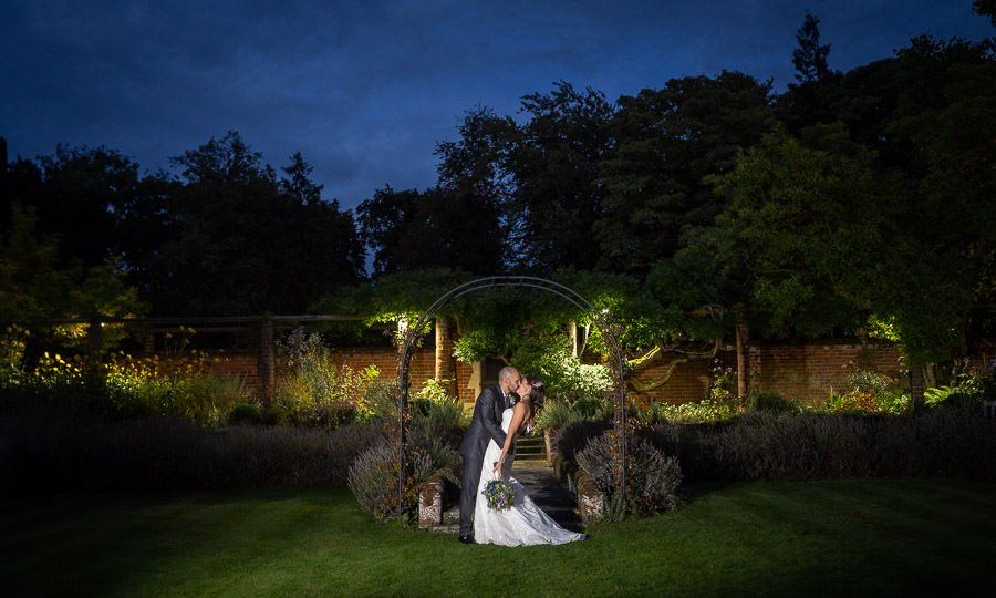 Bride and Groom embracing in the formal gardens at Lanwades Hall Wedding, photographed at night.