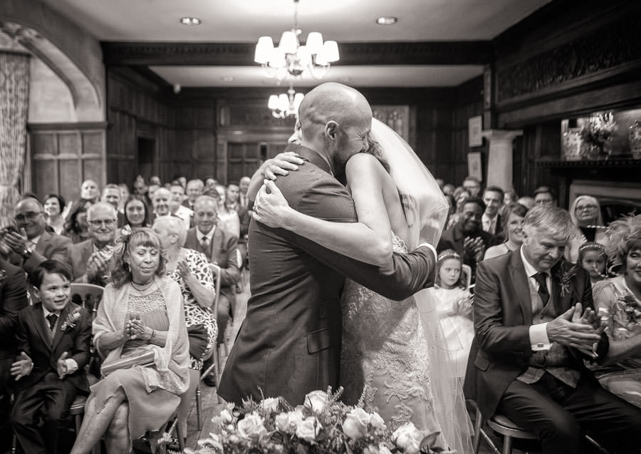 Black and white wedding photograph of bride and groom embracing at Lanwades Hall Wedding