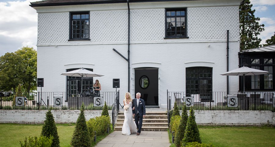 Bride and father walking towards the ceremony at Swynford Manor Wedding