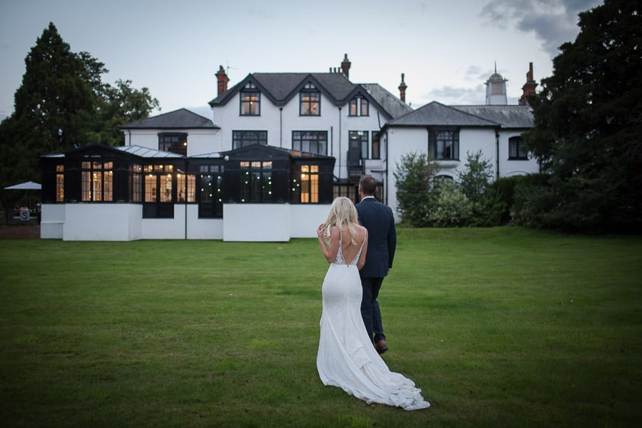 Bride and groom walking towards Swynford Manor