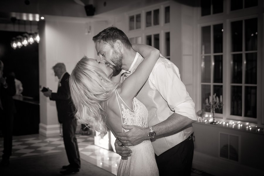 Black and white image of groom and bride dancing and kissing at Swynford Manor Wedding