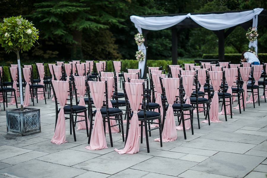 Beautifully decorated wedding chairs with light pink chair covers