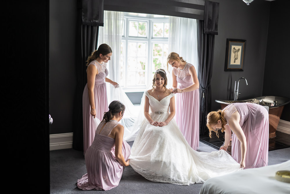 Bride dressed with her team of bridesmaids helping her with her dress