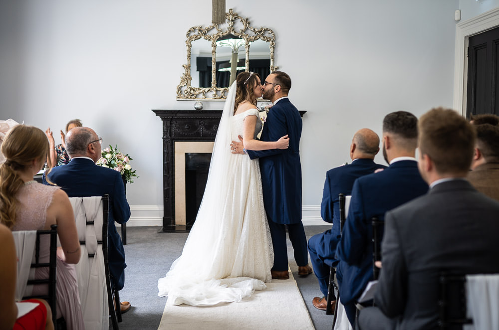 Bride and groom having their first kiss at swynford wedding