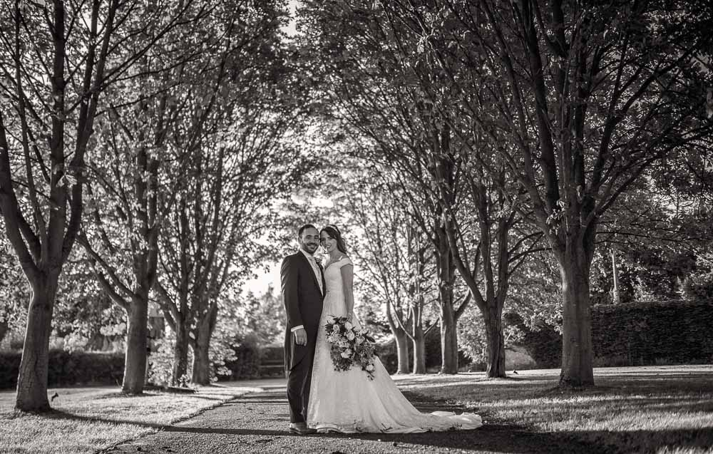 Formal portrait in black and white of bride and groom standing in a tree lined avenue at Swynford Wedding