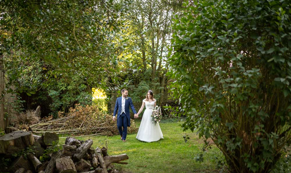 Bride and Groom hand in hand walking in grounds at Swynford Wedding