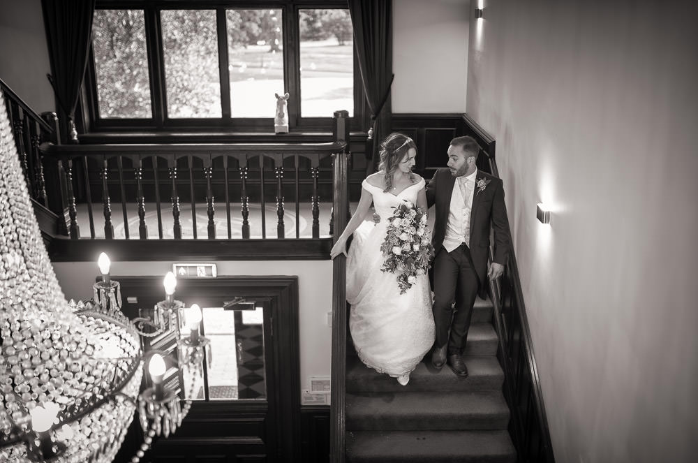 Black and white image of bride and groom walking down Swynford's staircase at Swynford Wedding
