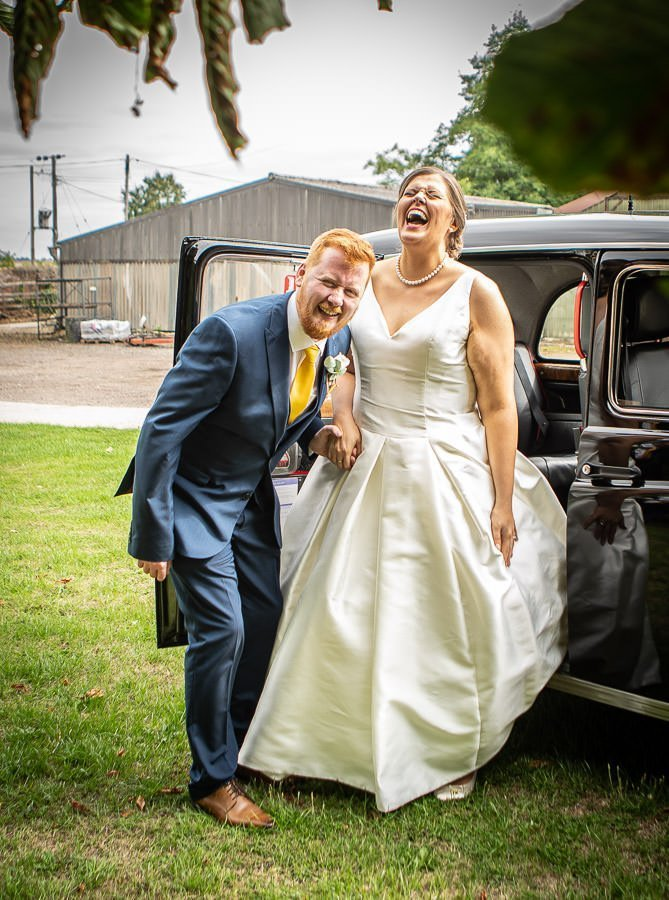 cambridge wedding photographer - shot of bride and groom laughing and smiling after ceremony