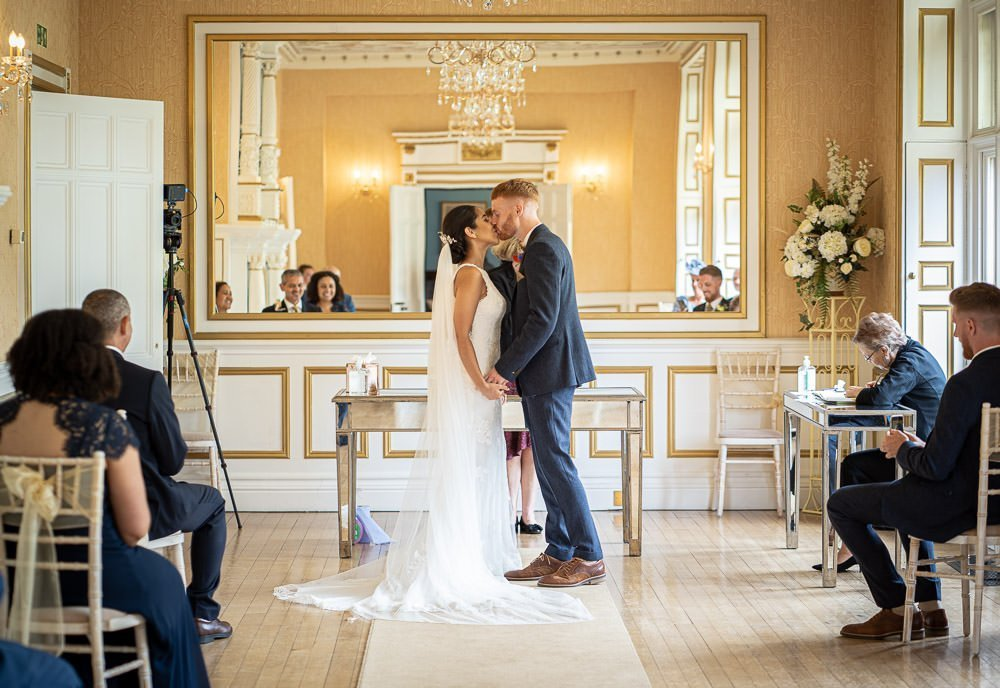 bride and groom kissing at ceremony at intimate wedding at Holmewood Hall