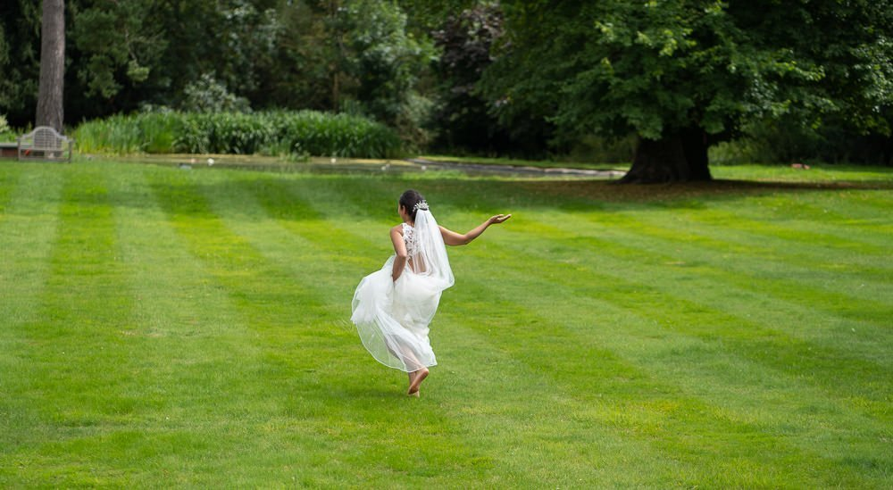 Bride running along lawn at intimate wedding at Holmewood Hall