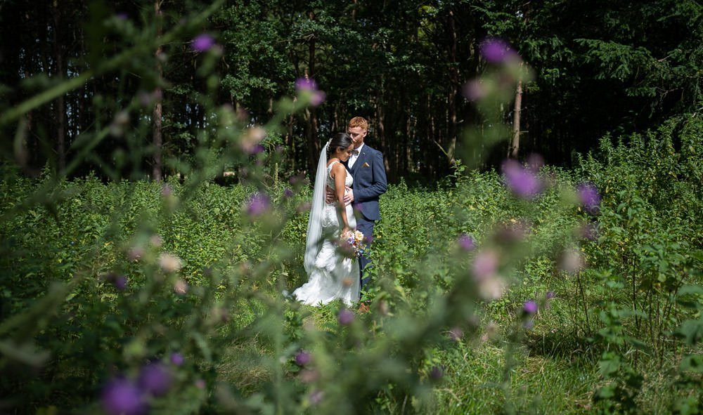 couple in wild flower meadow at intimate wedding at Holmewood Hall