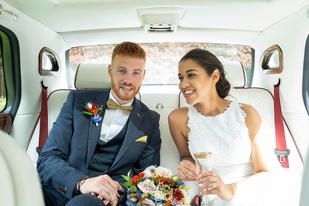 intimate wedding at Holmewood Hall, couple leaving together in wedding car.