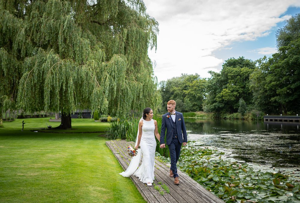 intimate wedding couple walking long river bank