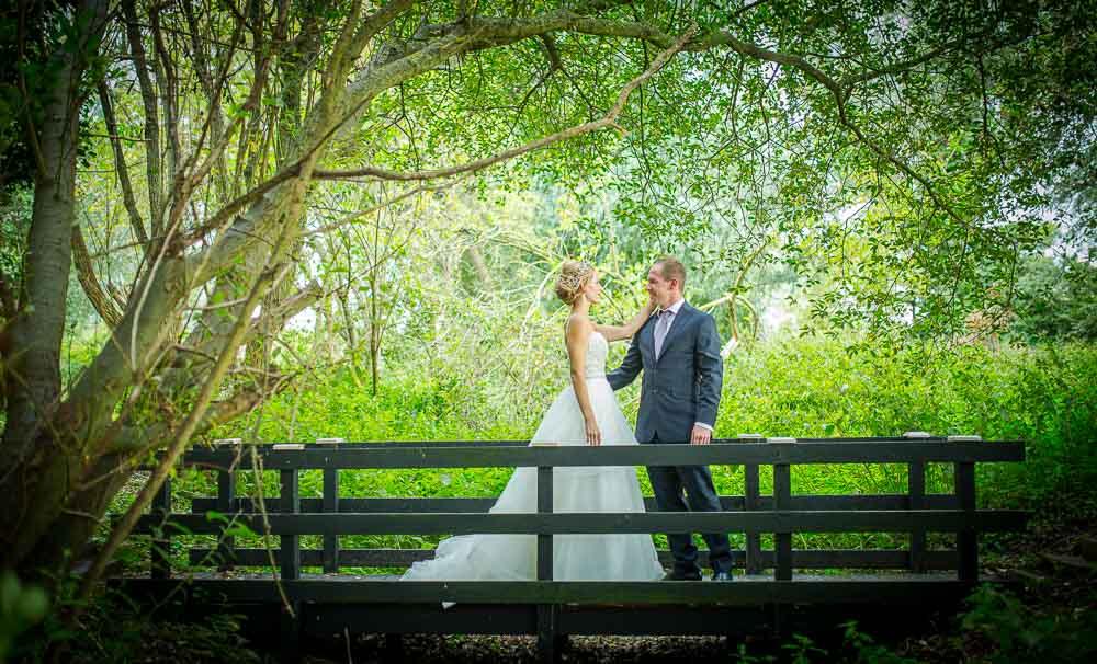 Bride walking towards her groom on a bridge, by Cambridge Wedding Photographer