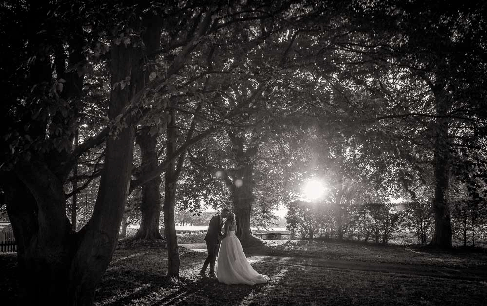 black and white sshot of bride and groom kissing in the wedding venue grounds, Cambridge Wedding Photographer at The Granary-Barns.