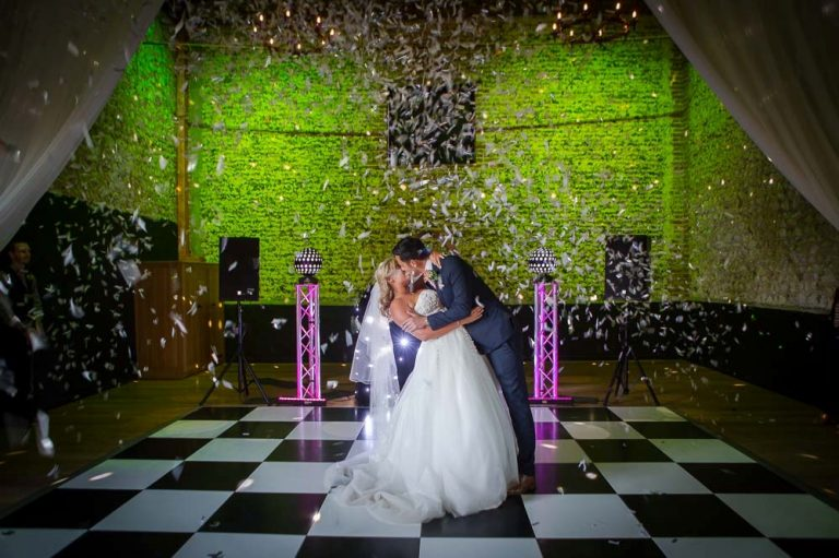 Bride and groom kissing during the first dance as confetti falls from above, at a granary-barns-wedding
