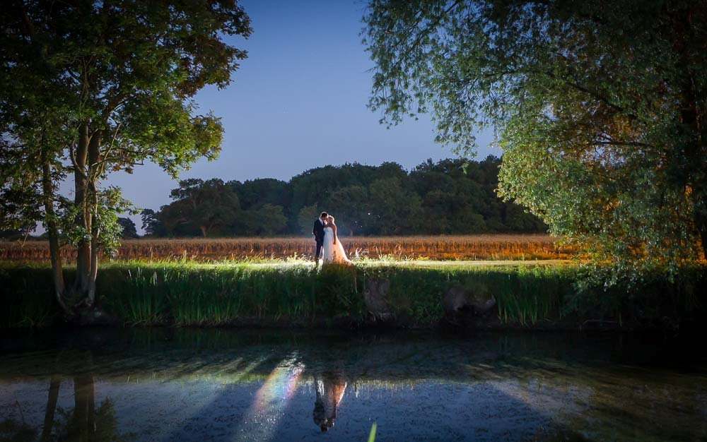 Night shot of bride and groom photographed by a lake Cambridge Wedding Photographer