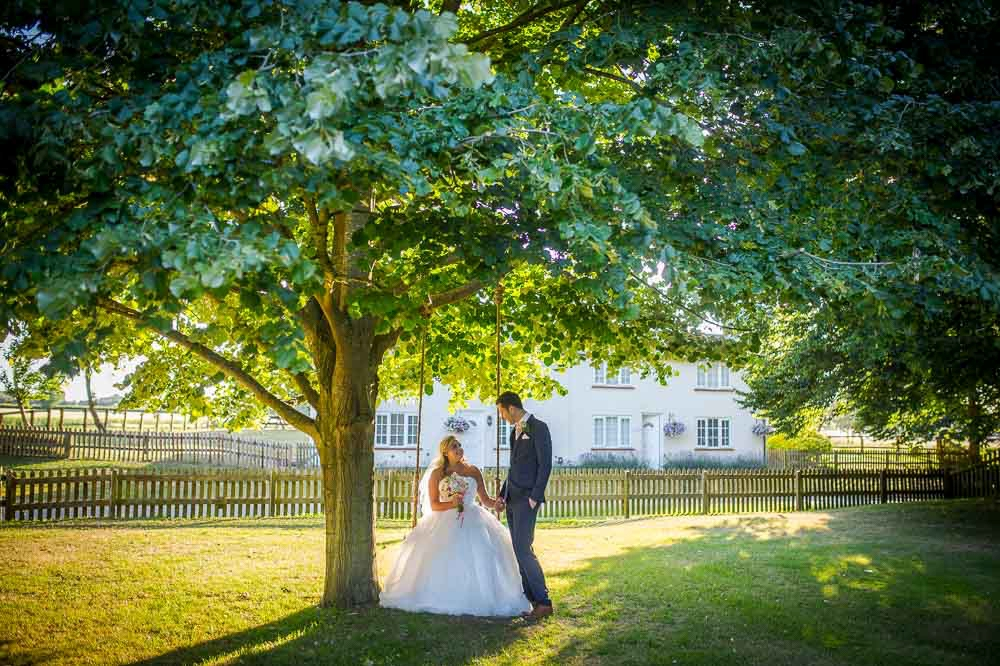 Bride on a swing, whil groom stands next to her photographed at Granay-Barns, photographed by Cambridge Wedding Photographer