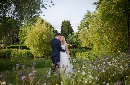 Bride and Groom about to kiss in a wild flower meadow, at The Granary Estates