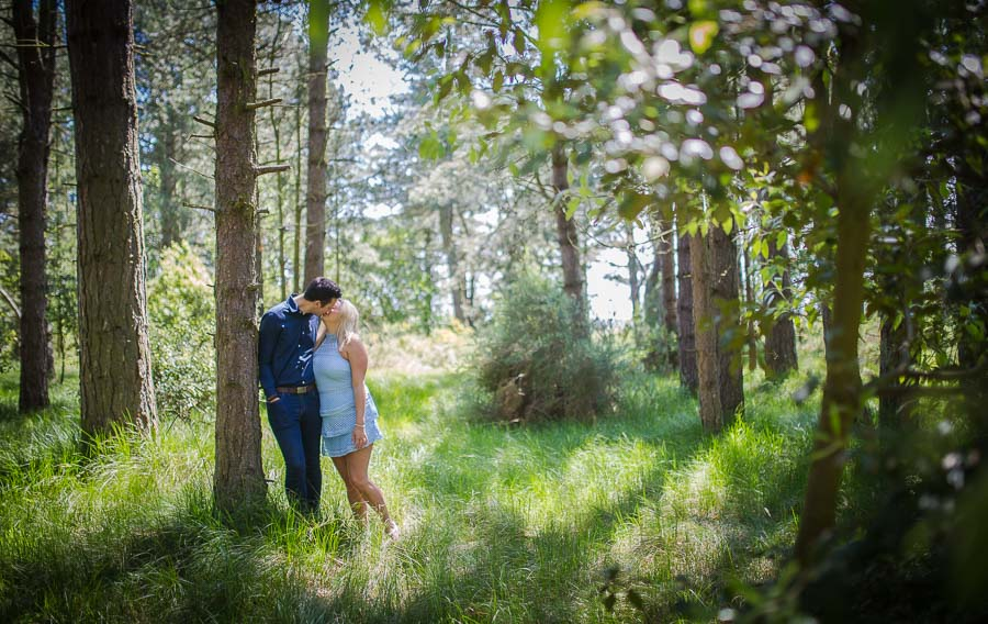 Norfolk Coast engagement shoot featuring a couple, kissing, as he leans against a tree.