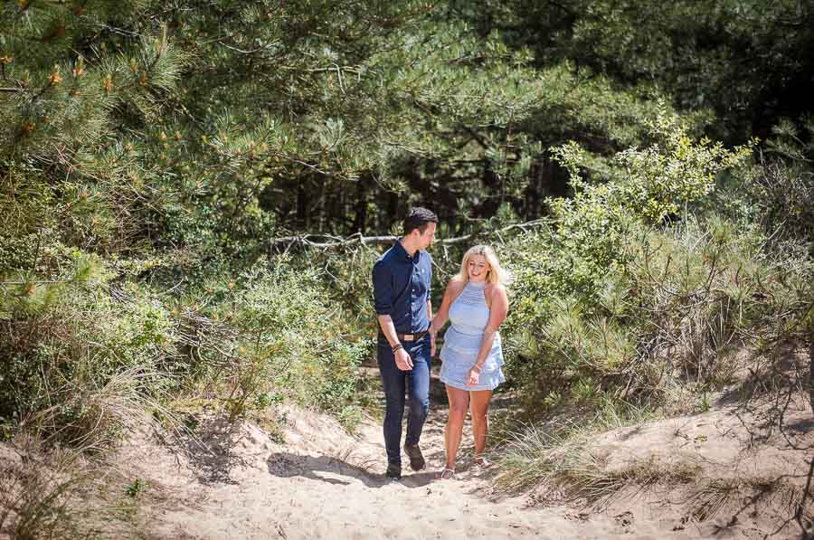 couple emerging from the pine forest and to to the beach during their norfolk coast engagement shoot