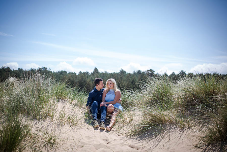 couple sitting in the sand dunes, during their norfolk coast engagement shoot